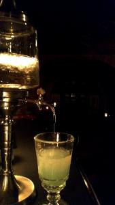 Aus einem Wasserspender plätschert Wasser in ein Absintheglas